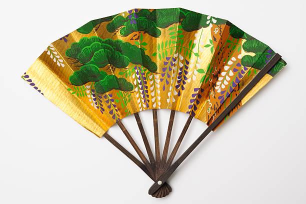 isolierte schuss von golden japanischer faltfächer auf weißem hintergrund - japanischer fächer stock-fotos und bilder