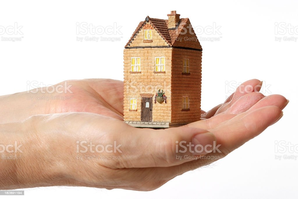 Isolated shot of holding a toy house against white background royalty-free stock photo