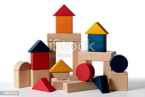 A partially constructed home, built from colorful wood blocks building isolated on white background.