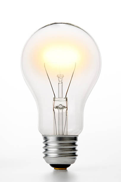 isolated shot of illuminated light bulb on white background - light bulb stock pictures, royalty-free photos & images