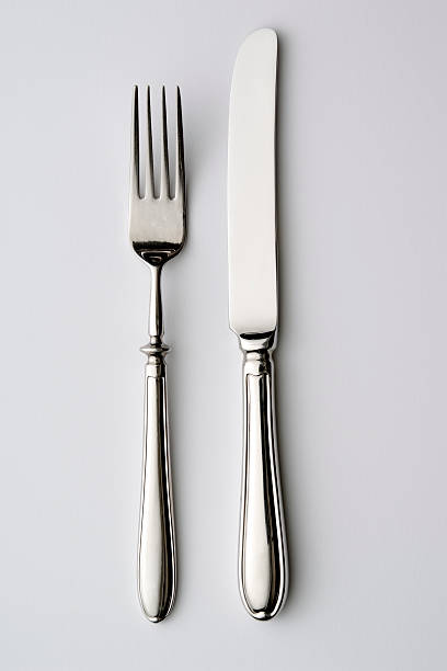 isolated shot of knife and fork on white background - table knife stock photos and pictures