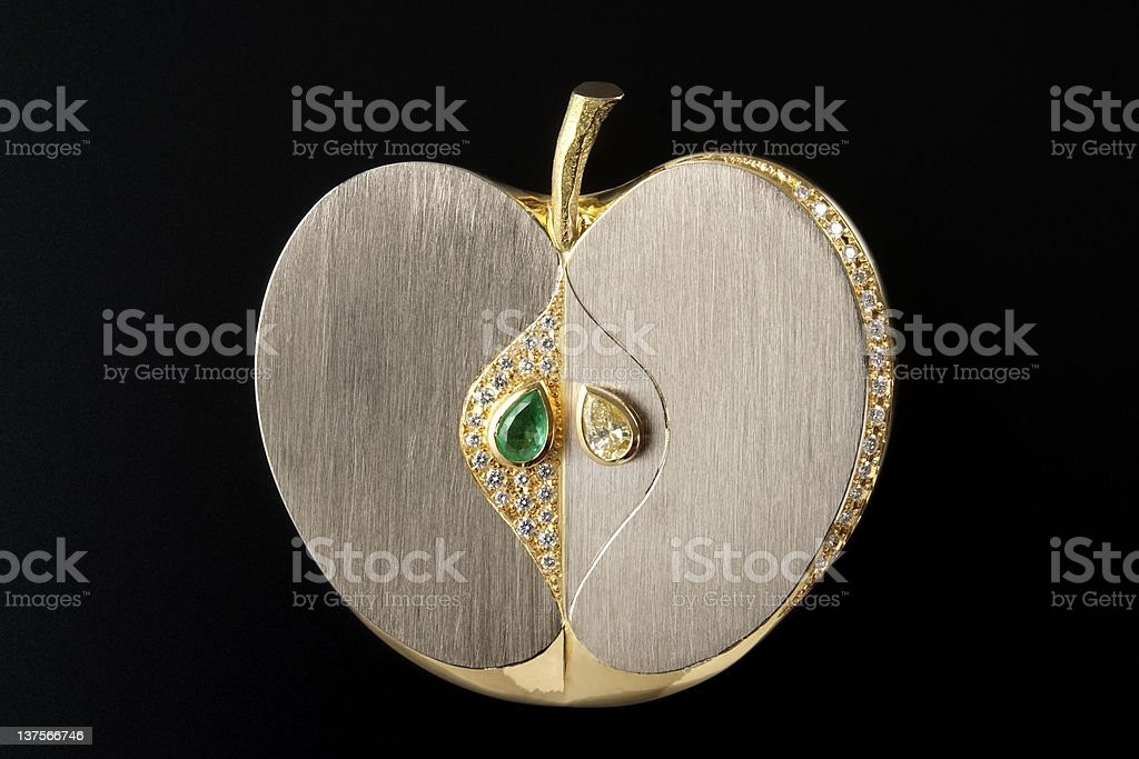 Isolated shot of luxury gold apple brooch on black background royalty-free stock photo