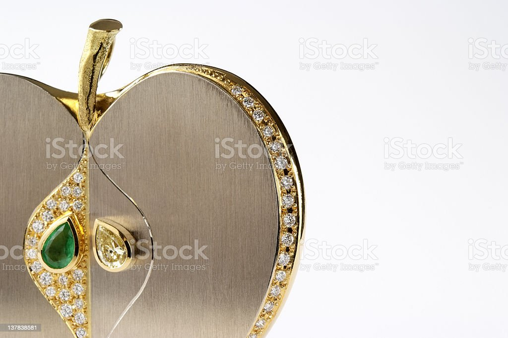 Isolated shot of luxury gold apple brooch on white background stock photo