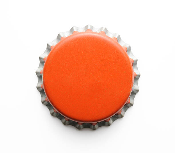 Isolated shot of old red metal bottle cap on white Old red metal bottle cap isolated on white background with clipping path. bottle cap stock pictures, royalty-free photos & images