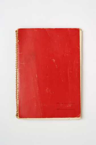 Isolated shot of old red spiral notebook on white background