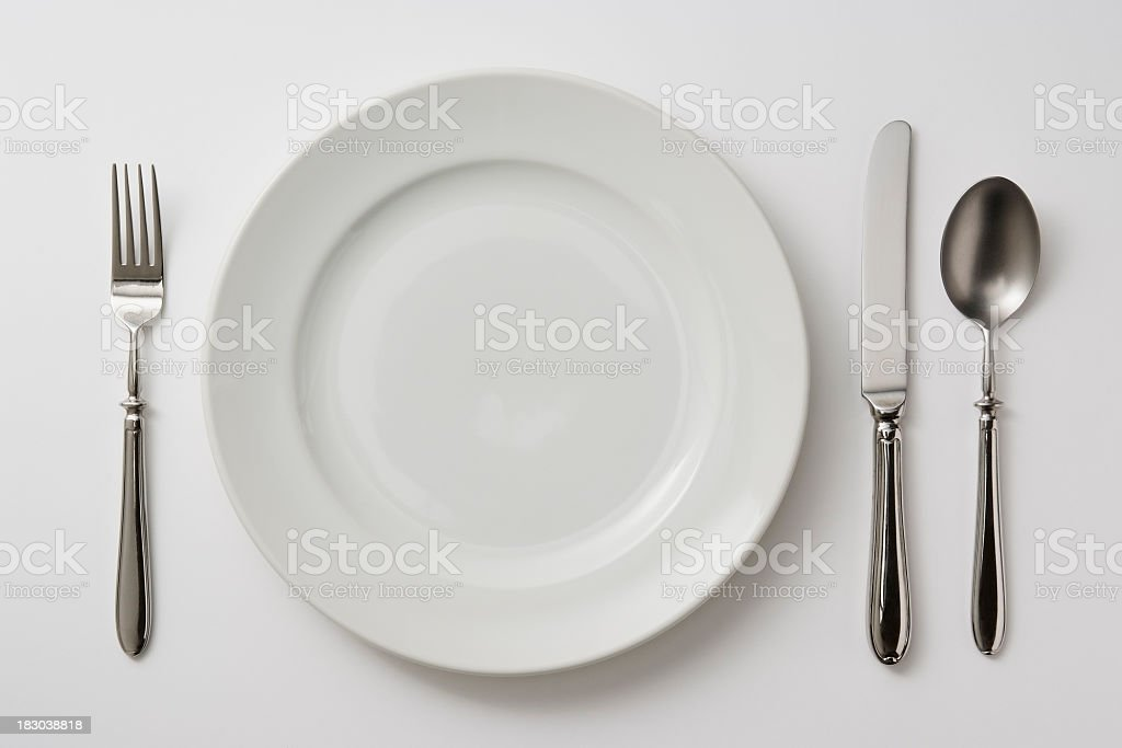 Isolated shot of plate with cutlery on white background stock photo