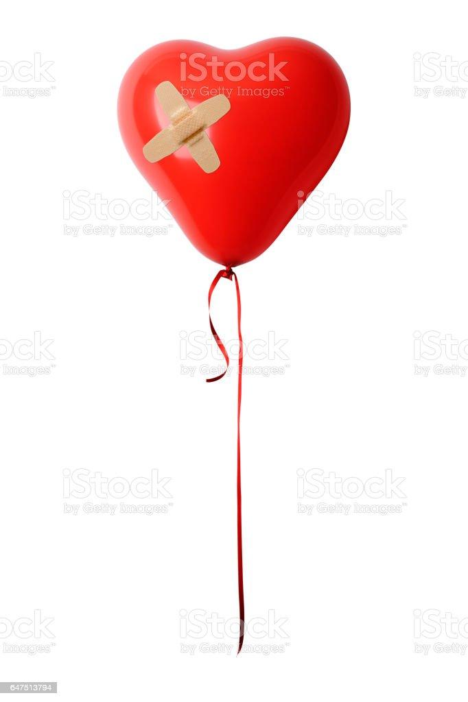 Isolated shot of red heart shape balloon with adhesive bandage on white background stock photo