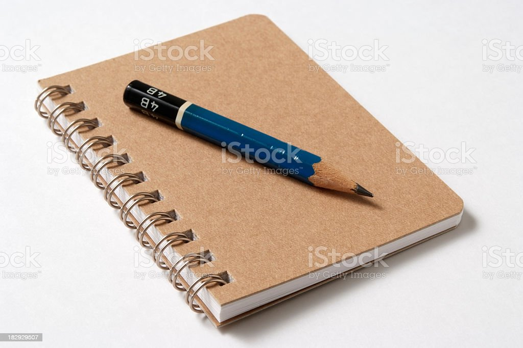 Isolated shot of spiral notebook with pencil on white background stock photo