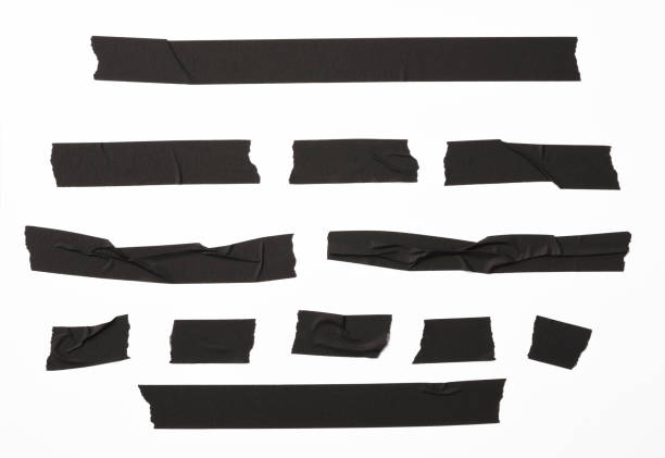 isolated shot of torn black adhesive tape on white background - adhesive tape stock photos and pictures