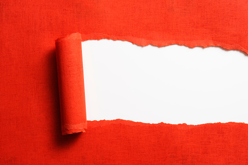 Close-up of torn red paper isolated on white background.