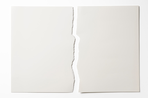 Close-up of blank torn piece of white paper isolated on white background with clipping path.