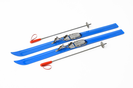 Isolated shot of vintage blue toy Skis & Poles on white background.