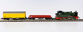 Vintage toy locomotive with railroad track on white background.