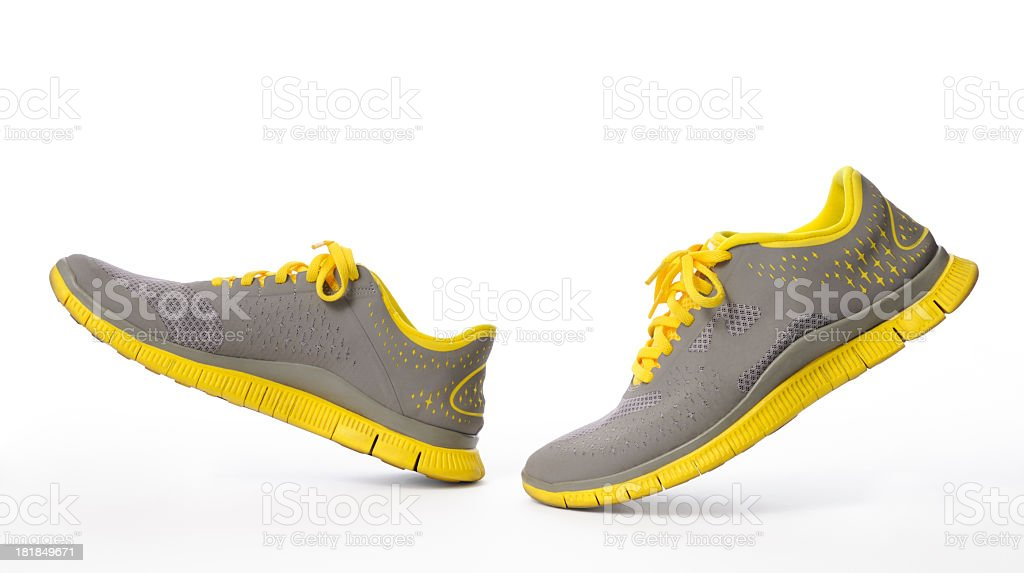 Isolated shot of walking yellow sneaker on white background stock photo