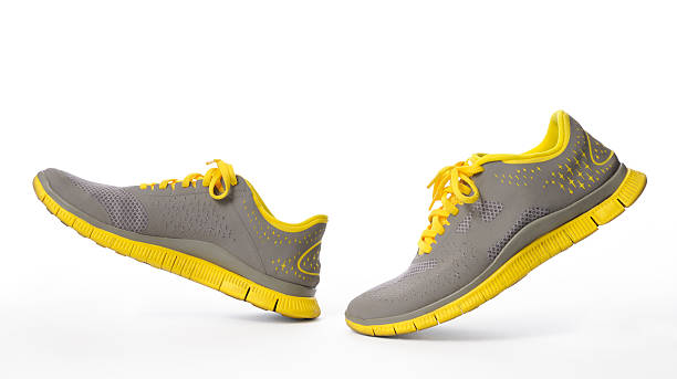 isolated shot of walking yellow sneaker on white background - running shoes stockfoto's en -beelden