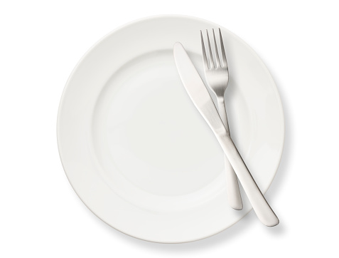 Overhead shot of white dinner plate with table knife and fork, isolated on white background.