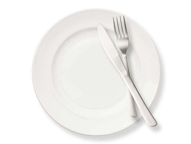Isolated shot of white plate with cutlery on white background stock photo