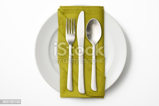 Overhead shot of white dinner plate and cutlery with green napkin, isolated on white background.
