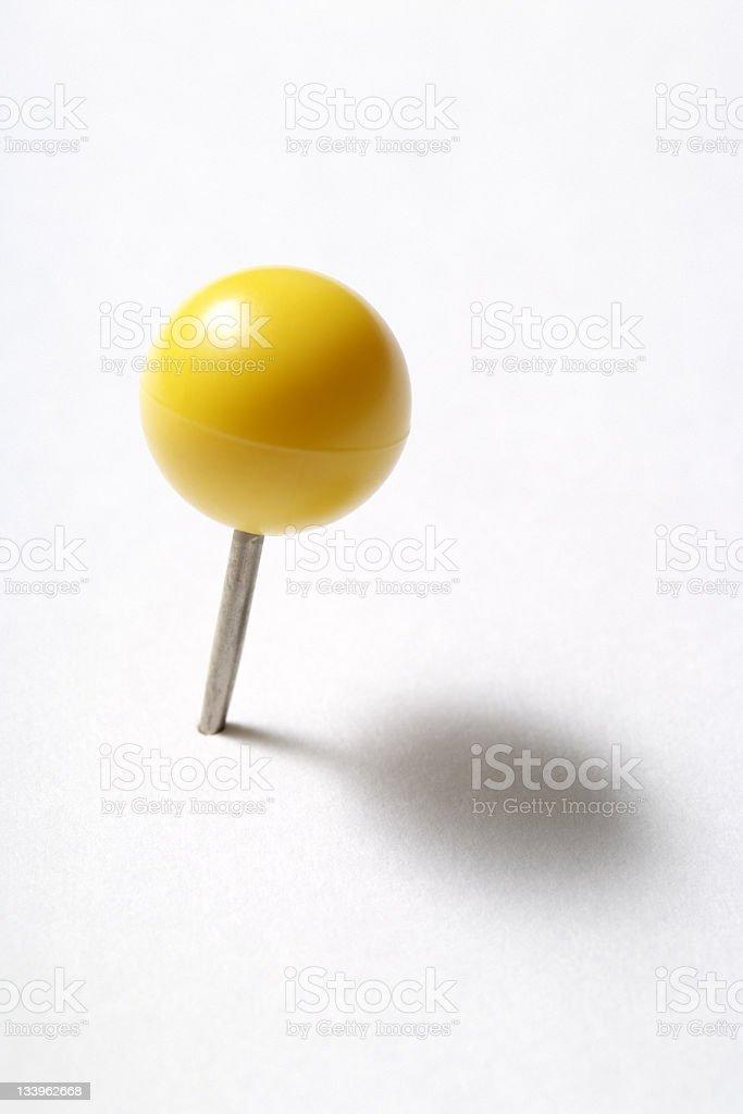 Isolated shot of yellow thumbtack on white background stock photo
