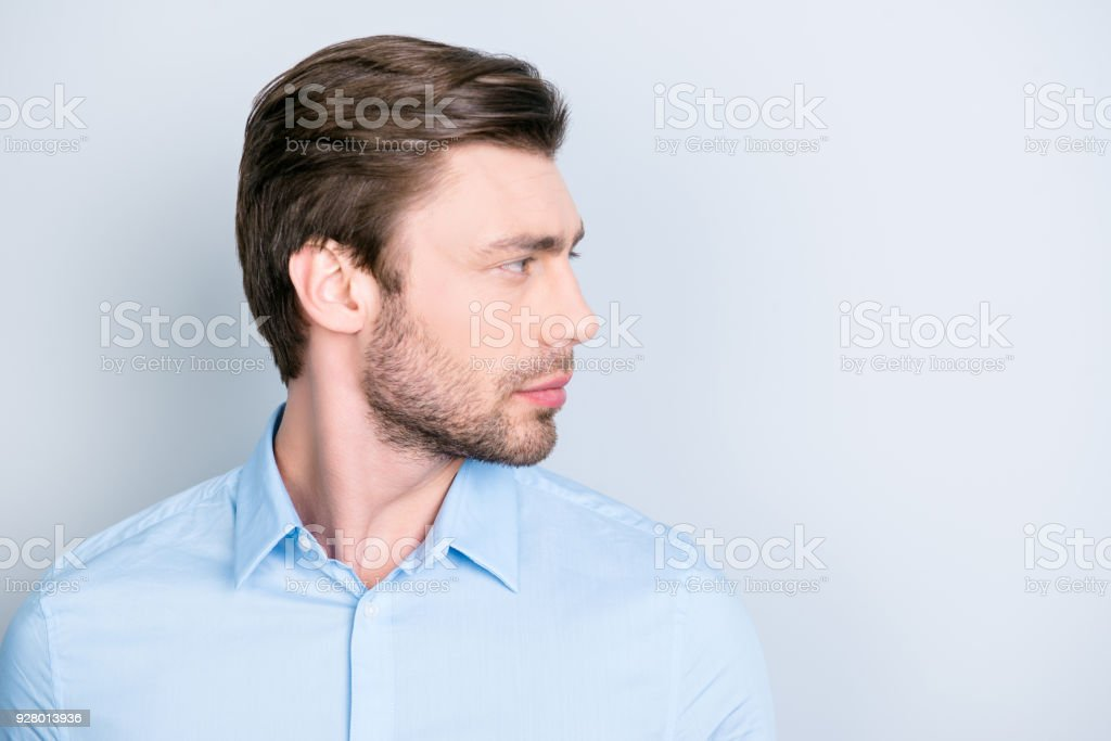 Isolated side view facial close up portrait of handsome confident serious man, looking to the side while standing on grey background stock photo