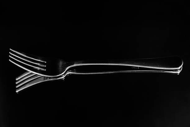Isolated silver fork reflection on black background stock photo