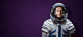 isolated simple astronaut uniform, scafandr and mask against the color wall background, wide banner. elements of this image furnished by nasa