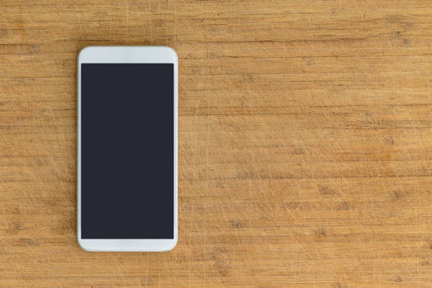 Isolated smart phone on scratched wooden table stock photo