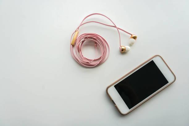 isolé de smartphone avec l'écouteur rose - écouteurs intra auriculaires photos et images de collection