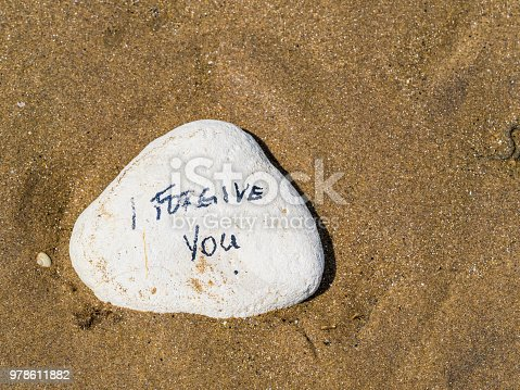 White stone in sand with proverb message written on it