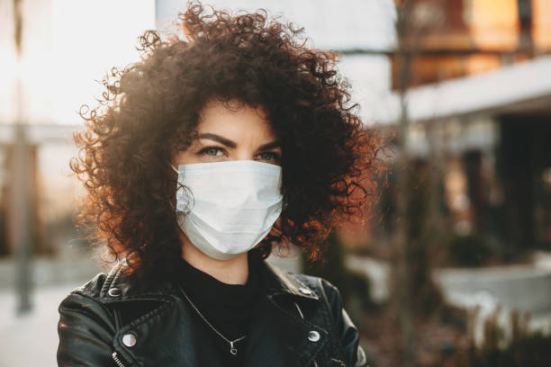 Isolated through a mask caucasian girl with nice curly hair is posing sadly outside while looking to camera stock photo