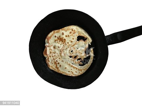 Isolated top view of a flawed crepe on a skillet with white background