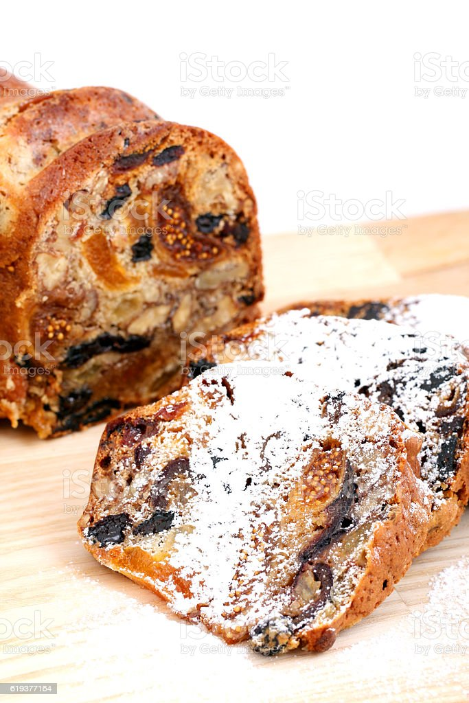 isolated traditional christmas stollen cake on wooden background stock photo