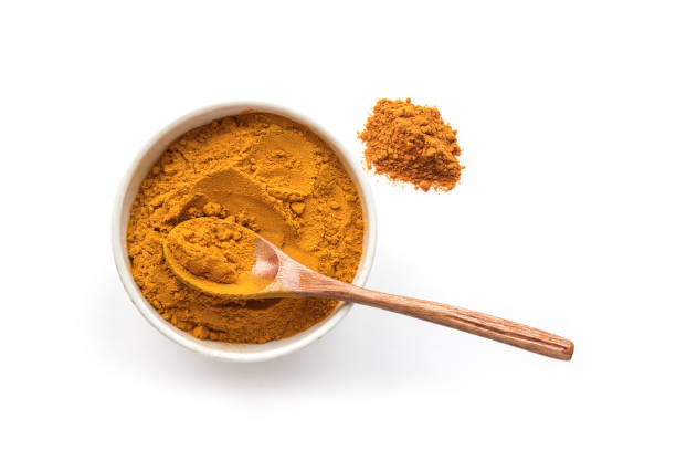 Isolated turmeric powder and wooden spoon. Top view. stock photo