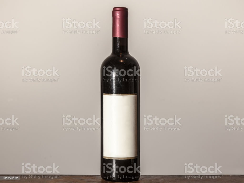 Picture of a bottle of red wine, isolated in front of a white...