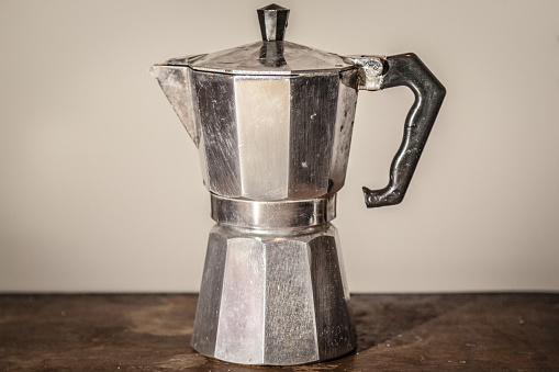 Isolated vintage moka pot on a white background standing on a retro wooden table. Mocha pots are the most used espresso coffee machines in Italy