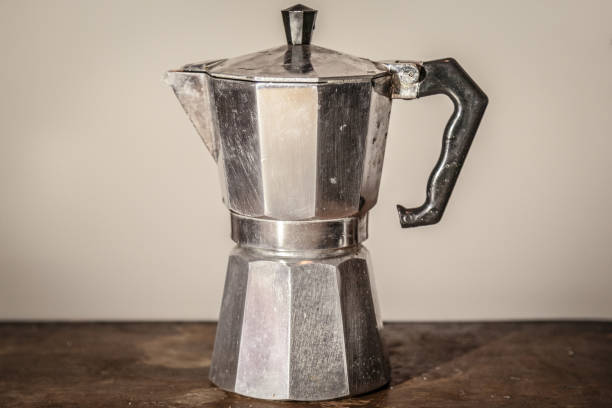 Isolated vintage moka pot on a white background standing on a retro wooden table. Mocha pots are the most used espresso coffee machines in Italy Picture of an old and used Italian espresso coffee machine of Moka pot style standing on a vintage wooden table, facing a white background coffee pot stock pictures, royalty-free photos & images