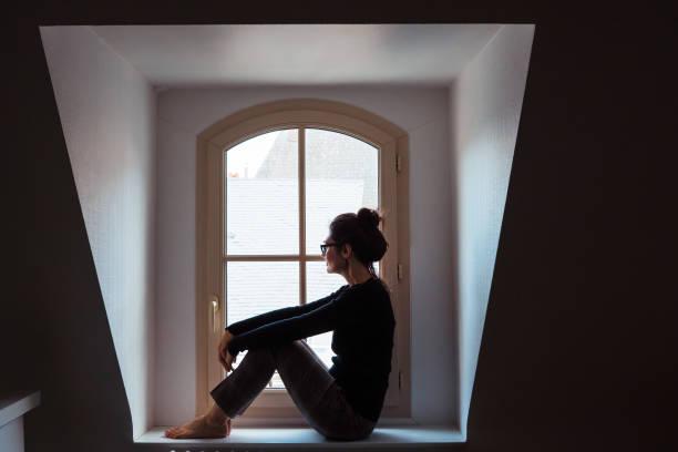 geïsoleerde vrouw ongerust die door het venster thuis kijkt. - claustrofobie stockfoto's en -beelden