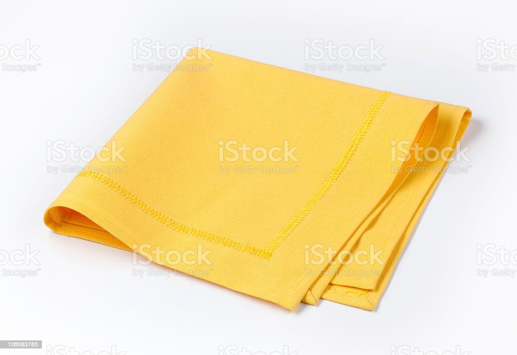 Isolated yellow napkin twice folded on white background stock photo