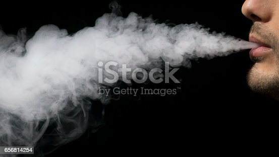 830035654 istock photo Isolated young man on a black background holding an electronic cigarette, vaping device, mod, e-cig. 656814254