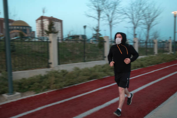 Isolated young man wearing mask and a hoodie running at a park stock photo
