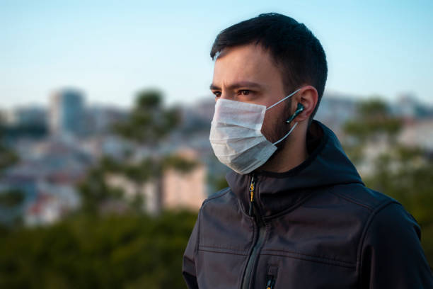 Isolated young man wearing mask looking towards in concern stock photo