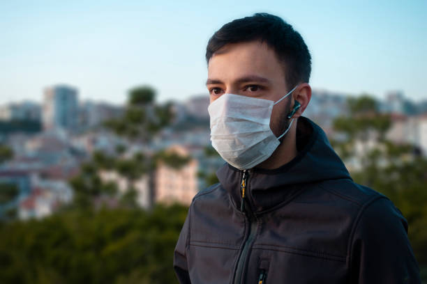Isolated young man wearing mask looking towards stock photo