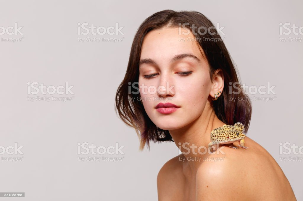 Isolation. A young dark-haired girl with short hair and bare shoulders. On her shoulder is an iguana gecko. stock photo