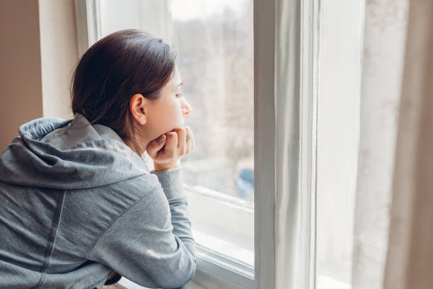 Isolation at home during coronavirus covid-19 pandemic. Woman looking at window. Stay safe at home on quarantine