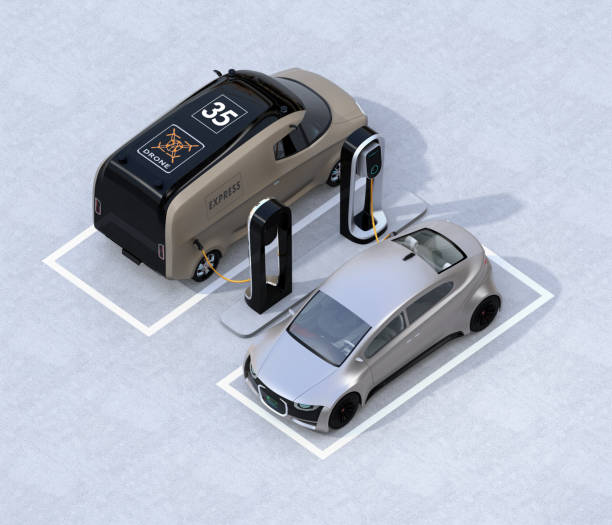Isometric view of electric delivery minivan and silver sedan charging at charging station stock photo