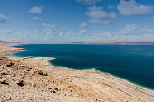 Beautiful scenic view from above along the dry rocky Dead Sea Coast of the West Bank Israel. Jordan Dead Sea Coast on the horizon. Dead Sea, Ein Gedi, Israel, Middle east.