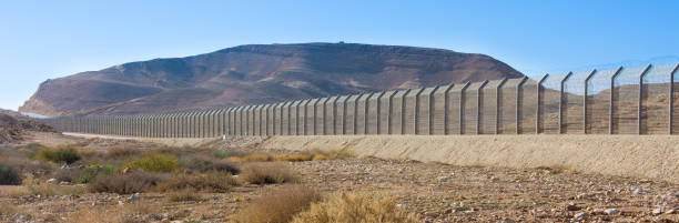 Israel Egypt border fence in the Negev and Sinai deserts The new border fence between Israel (Negev Desert) and Egypt (Sinai Desert) international border barrier stock pictures, royalty-free photos & images