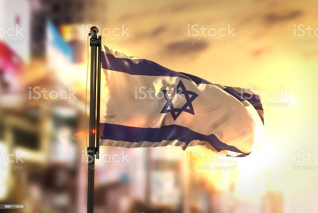 Israel Flag Against City Blurred Background At Sunrise Backlight stock photo