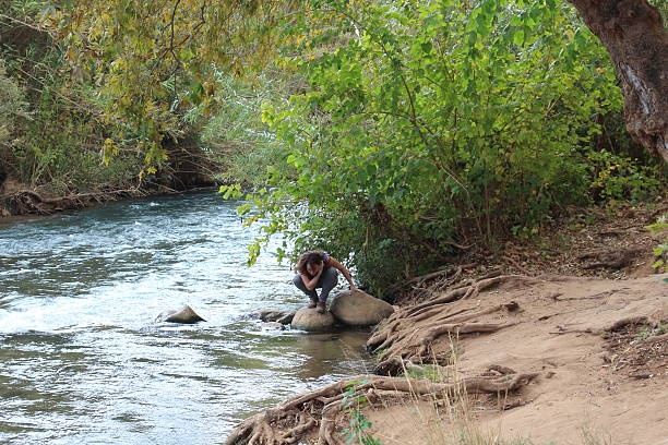 Israel Young female on the banks of Snir Stream stock photo