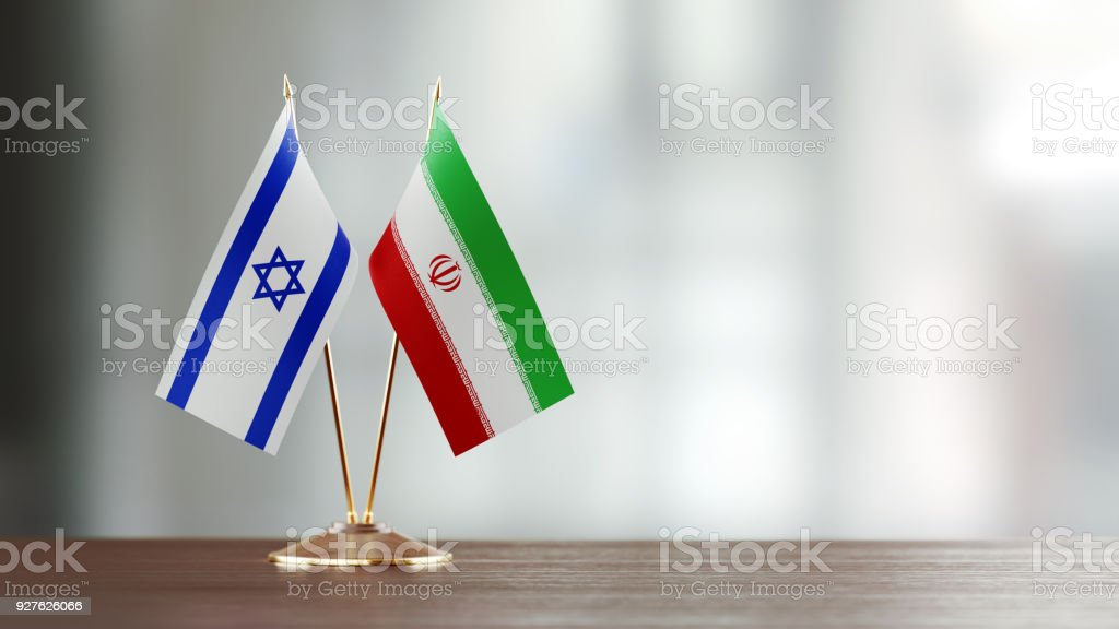 Israeli And Iranian Flag Pair On A Desk Over Defocused Background stock photo